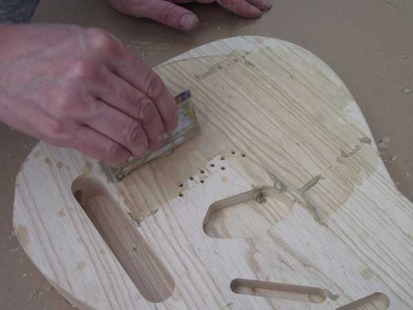 Applying grain filler to the front of the guitar body